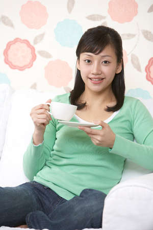 leisureliness: Young woman with cup of coffee, smiling, portrait LANG_EVOIMAGES