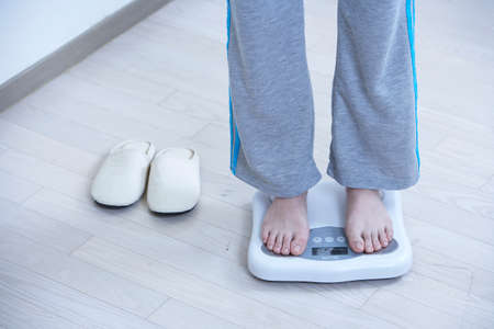 low section view: Woman standing on weighing scale, low section