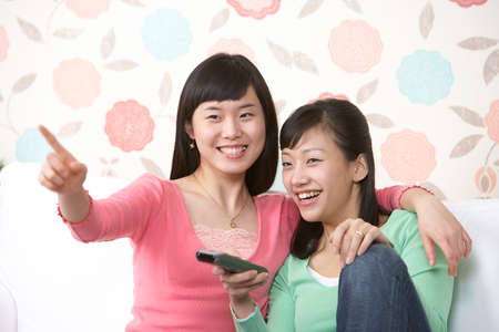 leisureliness: Two young women sitting on sofa, one using remote control LANG_EVOIMAGES