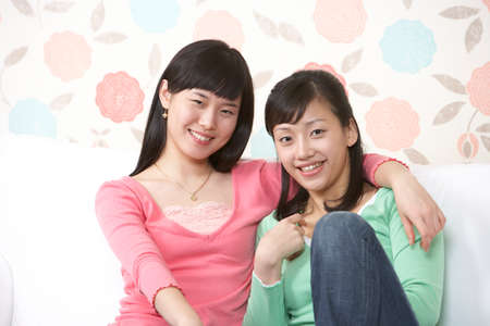 leisureliness: Two young women sitting on sofa, smiling, portrait