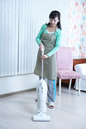 dark haired woman: Young woman using vacuum cleaner