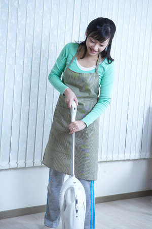 domesticity: Young woman using vacuum cleaner