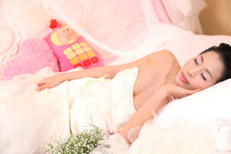 woman lying down: Woman lying down on bed LANG_EVOIMAGES