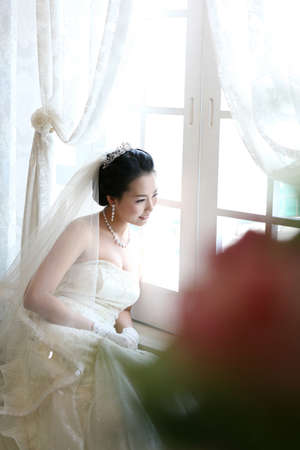 joyfulness: Young woman in wedding dress sitting by window