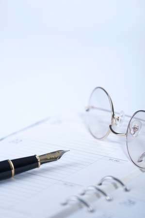 differential focus: Close up of diary with pen and spectacles LANG_EVOIMAGES