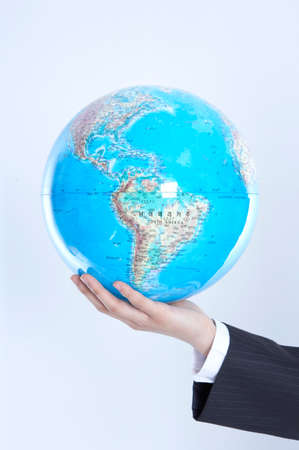 formal wear clothing: Person holding model of globe against white background