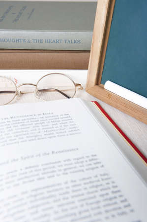 western script: Book with glasses slate chalk and stack of books LANG_EVOIMAGES