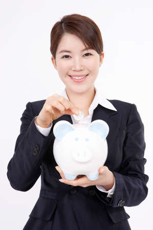 depositing: Young woman inserting coin into piggy bank