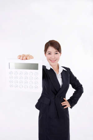 contentment: Portrait of a young woman holding calculator with hand on hip LANG_EVOIMAGES