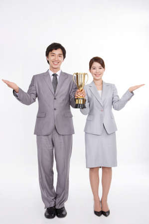 joyfulness: Portrait of businessman and businesswoman holding loving cup against white background