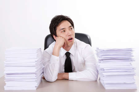 frustrating: Businesswoman sitting at desk by stacks of documents