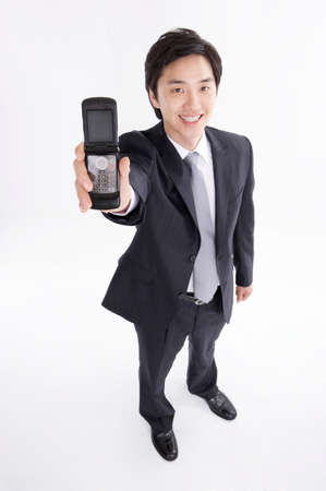 formal wear clothing: Portrait of a cheerful businessman with mobile phone