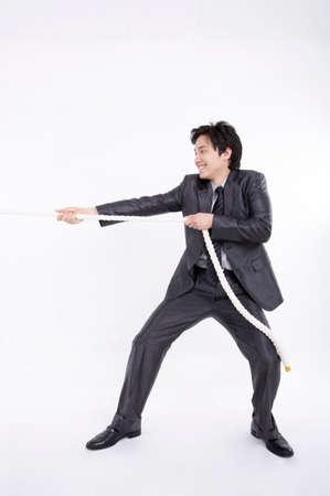 legs apart: Hombre de negocios alegre cuerda tirando