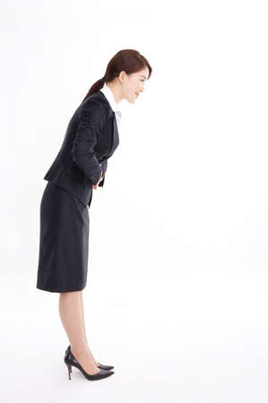 formal wear clothing: Young businesswoman standing against white background