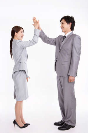 formal wear clothing: Businessman and woman high-fiving LANG_EVOIMAGES