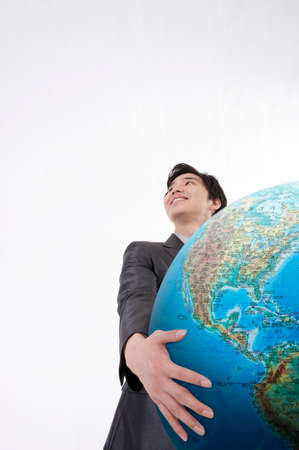 low angle views: Businessman holding globe against white background