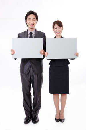 formal wear clothing: Portrait of businessman and woman holding blank card