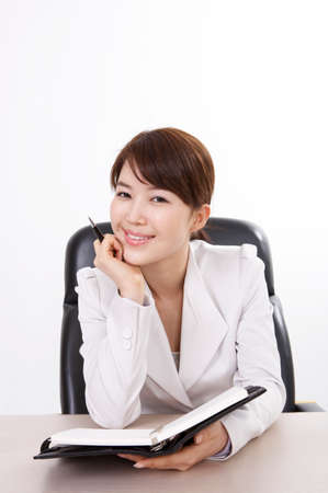 contentment: Portrait of a businesswoman with pen and diary at desk LANG_EVOIMAGES