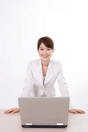 portraiture: Portrait of businesswoman standing in front of a laptop