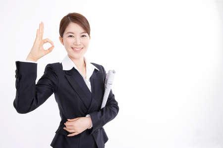 broadsheet: Portrait of a businesswoman making ok sign LANG_EVOIMAGES