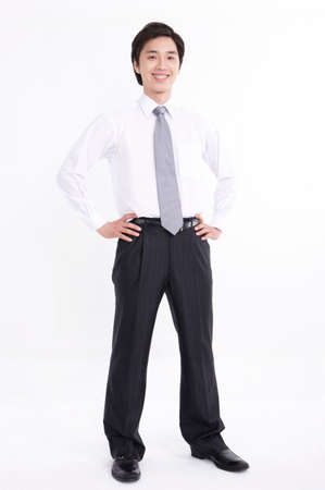 formal wear clothing: Young man standing with hands on hips