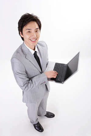 cheerfulness: Portrait of a cheerful young businessman using laptop