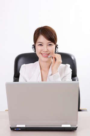 hands free: Empresaria alegre con la computadora port�til usando dispositivo de manos libres