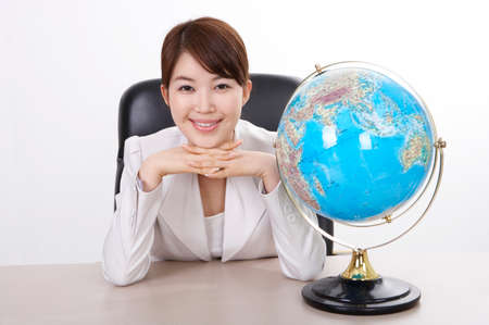 joyfulness: Cheerful businessman sitting by globe, portrait
