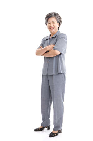 standing against: Businesswoman standing against white background, smiling
