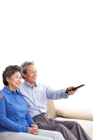 arts culture and entertainment: Mature couple sitting on sofa and watching television, smiling , portrait