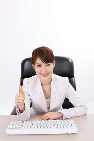 cheerfulness: Portrait of a cheerful businesswoman sitting with computer keyboard LANG_EVOIMAGES