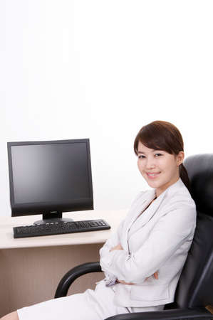 cheerfulness: Cheerful young businesswoman sitting with laptop