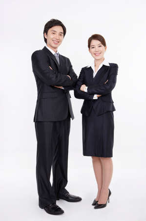 contentment: Portrait of a cheerful young business couple standing with arms crossed