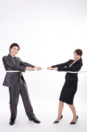 opposite: Businessman and woman pulling on opposite ends of rope LANG_EVOIMAGES