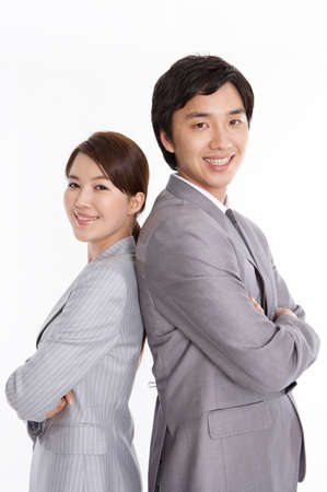 cheerfulness: Portrait of a cheerful young business couple standing with arms crossed
