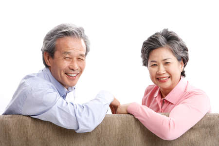 joyfulness: Mature couple sitting together on sofa, smiling, portrait