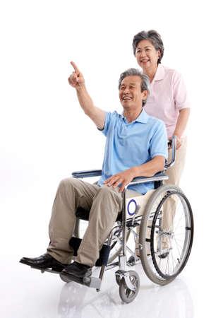empujando: Mujer que empuja al hombre en silla de ruedas, sonriente, retrato