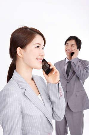 telefonos movil: Alegre pareja de negocios joven que usa los tel�fonos m�viles LANG_EVOIMAGES
