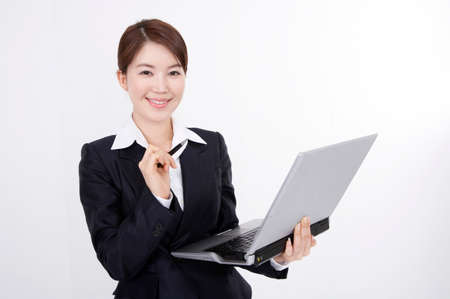 cheerfulness: Portrait of a cheerful young businesswoman using laptop