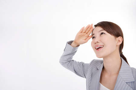 joyfulness: Young businesswoman saluting, smiling LANG_EVOIMAGES