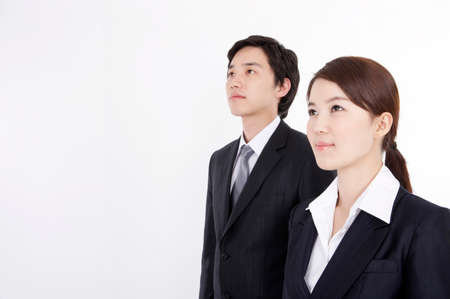 contentment: Young business couple standing side by side, smiling
