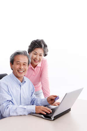 portraiture: Senior couple using laptop LANG_EVOIMAGES