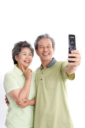 leisure wear: Mature couple photographing themselves, smiling LANG_EVOIMAGES