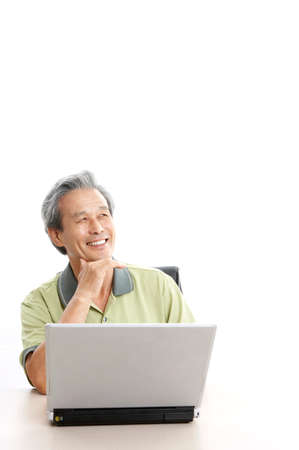 joyfulness: Mature man using laptop, smiling, looking up