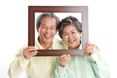 looking through an object: Mature couple peering through wooden frame, smiling, portrait