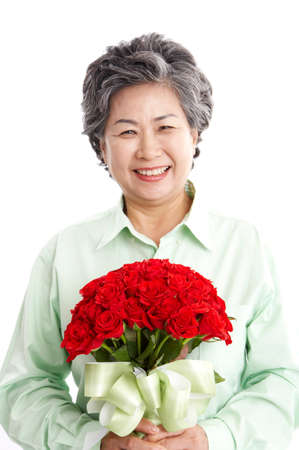 portraiture: Mature woman holding a bunch of flowers, smiling, portrait LANG_EVOIMAGES