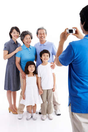 mid adult: Mid adult man photographing family LANG_EVOIMAGES