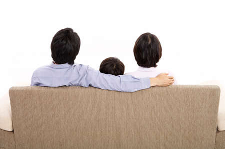 joyfulness: Father and mother with son sitting on sofa LANG_EVOIMAGES