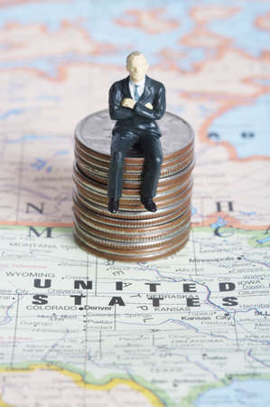 formal wear clothing: Stack of coins with businessman figurine over world map LANG_EVOIMAGES