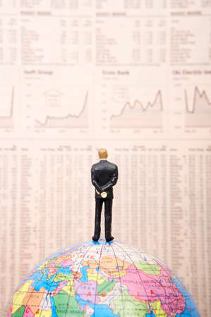 stock listing: Male figurine on globe facing financial newspaper